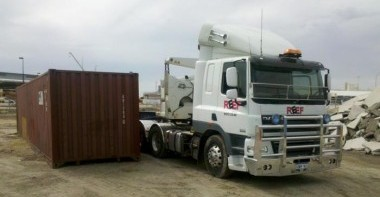 Side loader dropping shipping container off