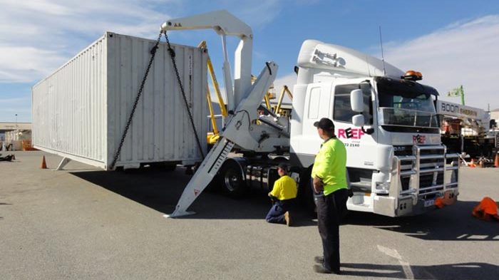 Image of side loader in action unloading a 40ft sea container