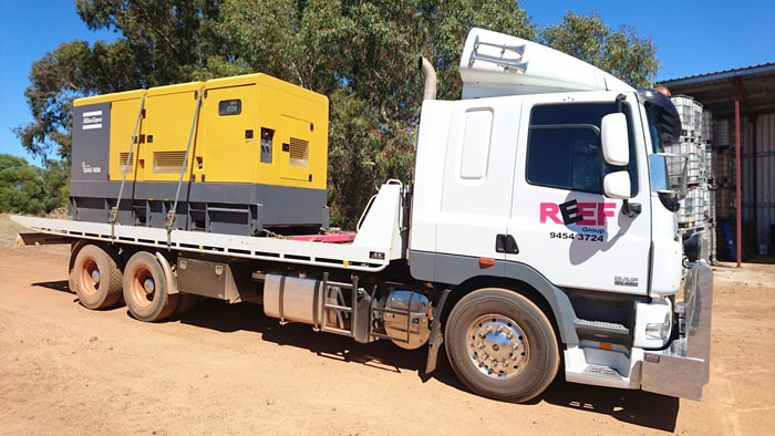 Tilt Trays truck Perth carrying yellow container