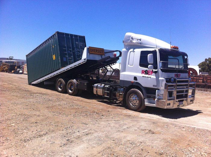 Slide Truck in the process of loading large shipping container
