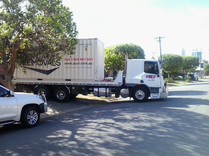 Tilt Tray Truck exiting driveway with large container