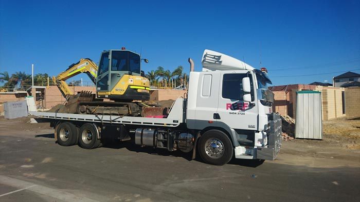 Tilt Tray trucking transporting crane from construction site