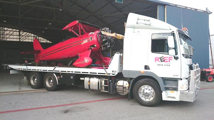 Reef Groups Slide Truck carrying a small airplane out of garage