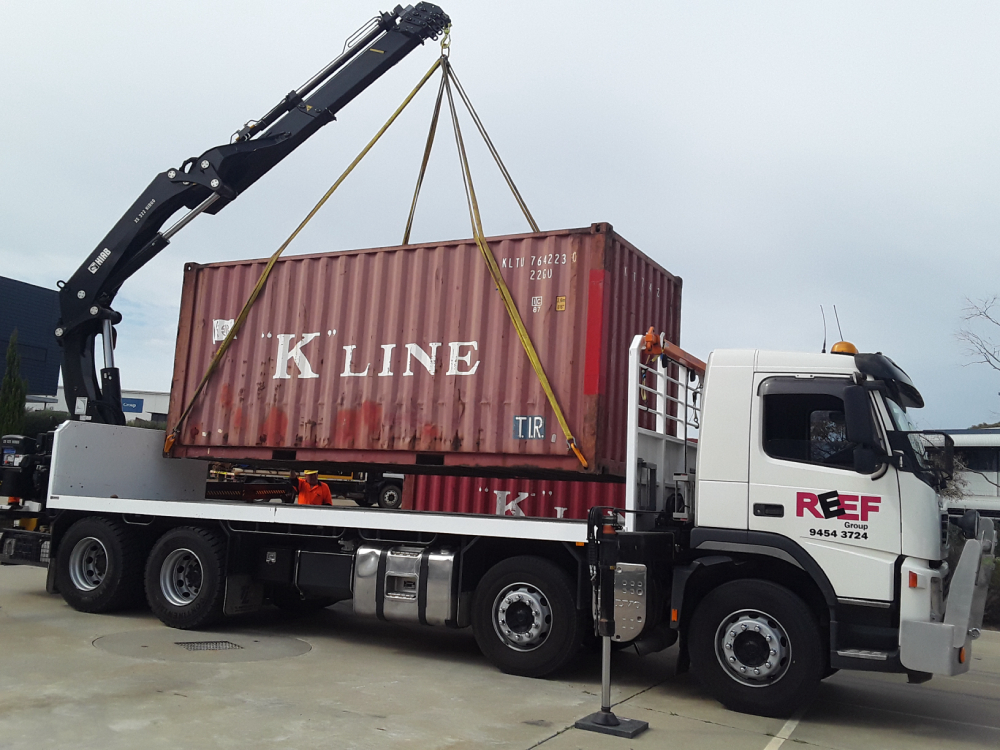 Sea container being dropped onto hiab truck