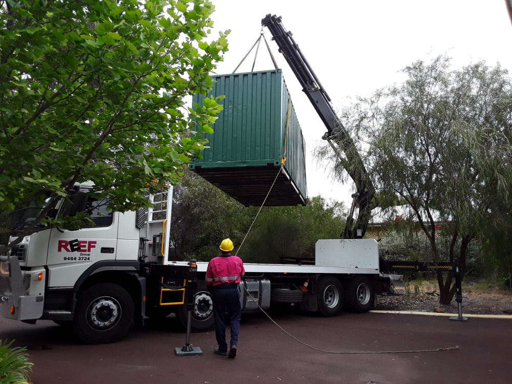 hiab lifting a container and man standing in front